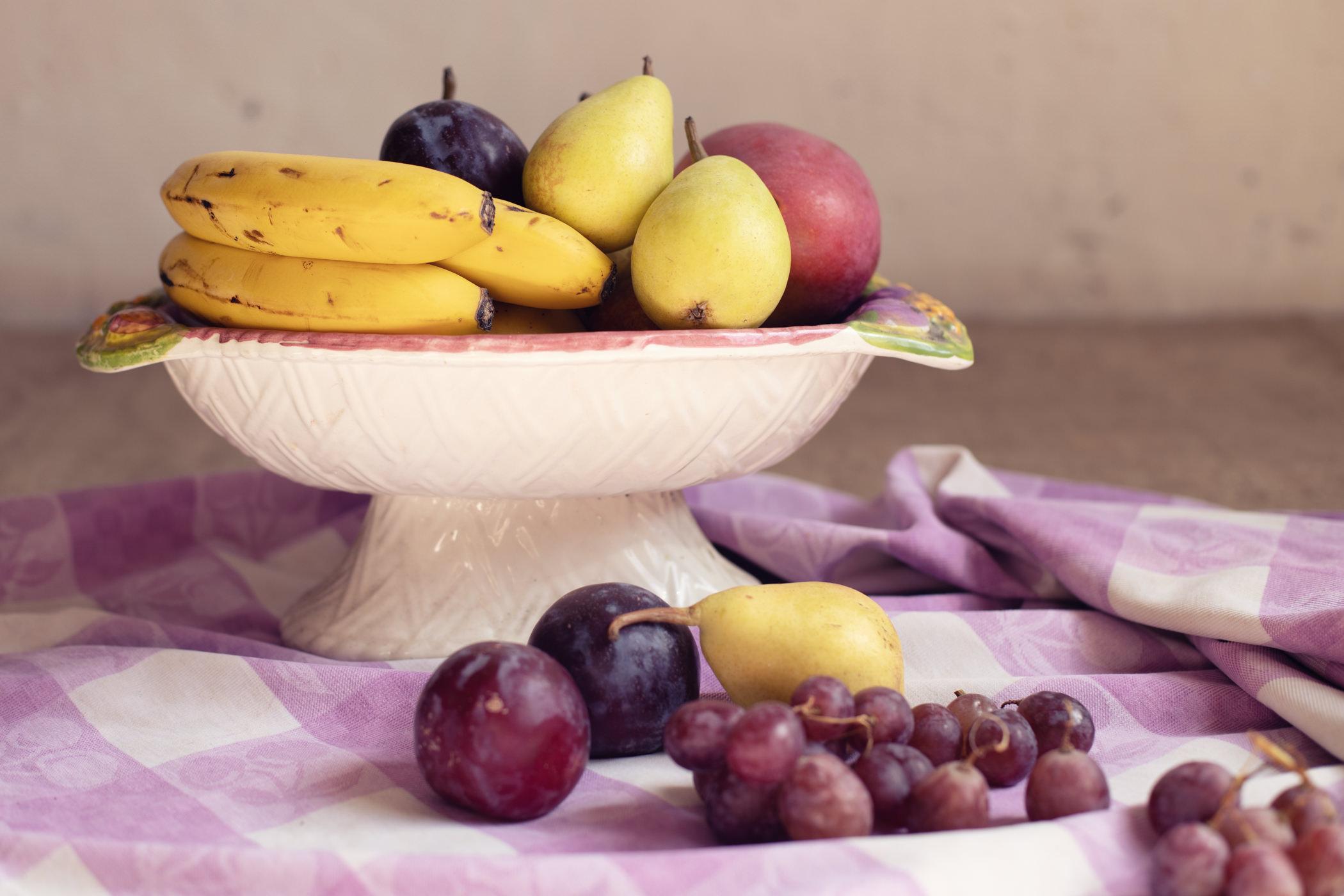 Bodegón de frutas clásico, con plátanos, peras, ciruelas y uvas