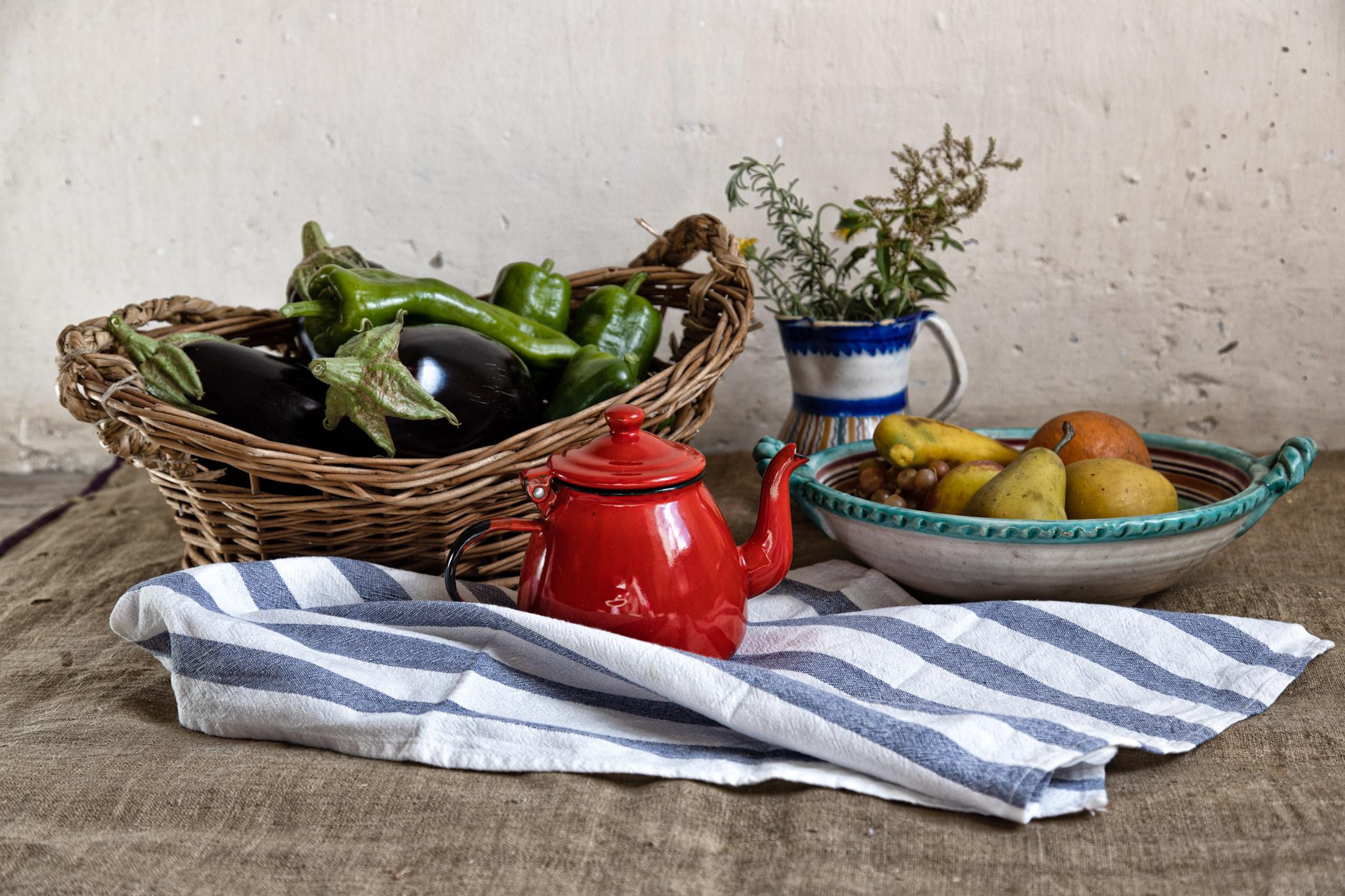 Bodegón rústico sobre saco, con cafetera roja, berenjenas y frutas de plástico