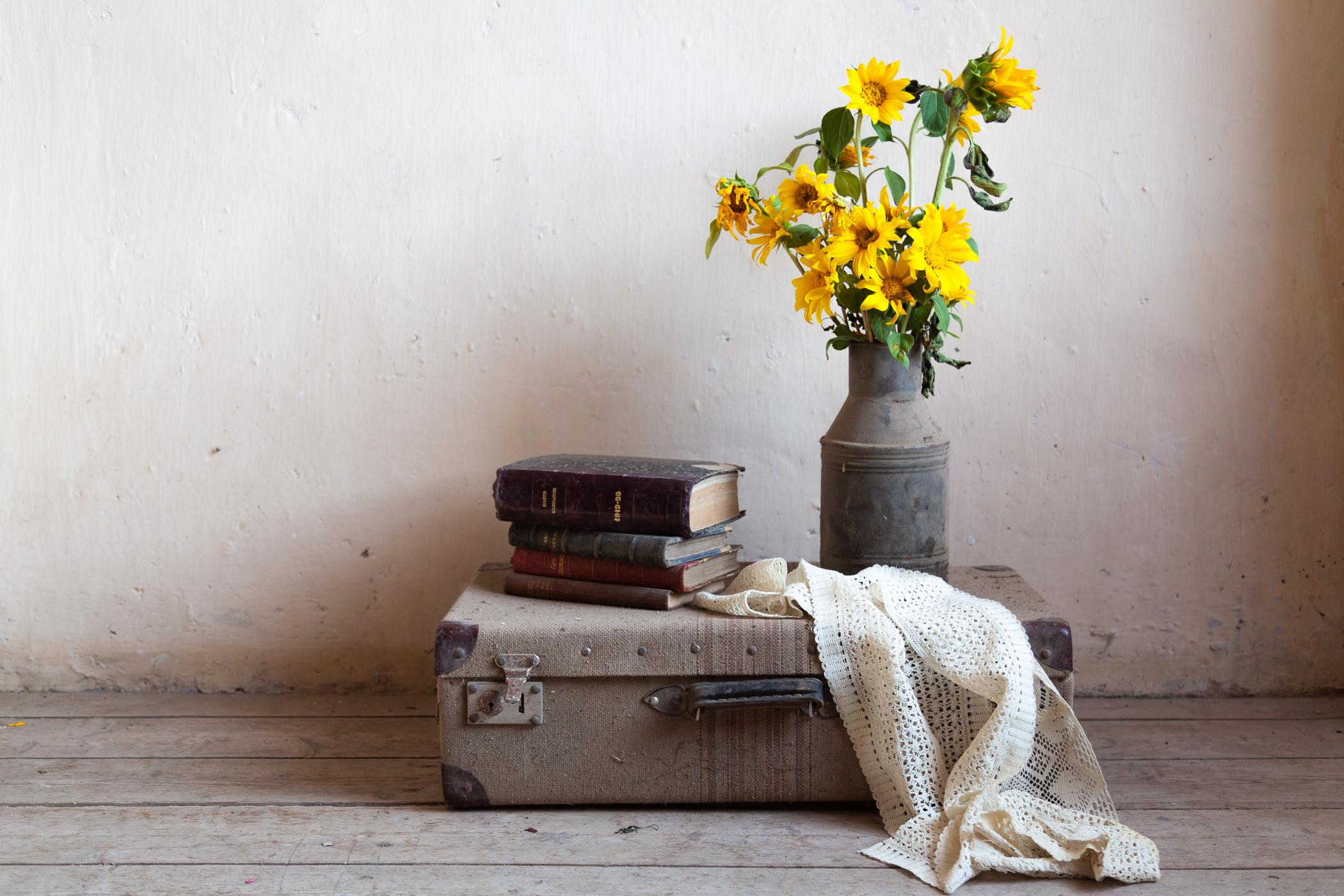 Bodegón con maleta, libros y girasoles